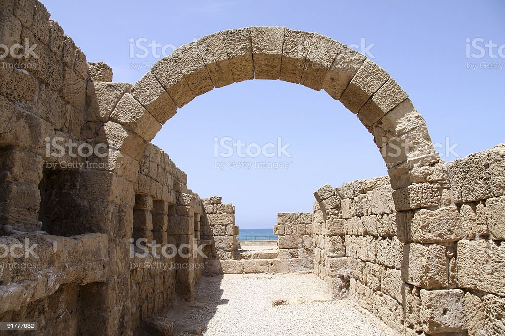 Ancient arcade made of rocks sitting alone the ocean royalty-free stock photo