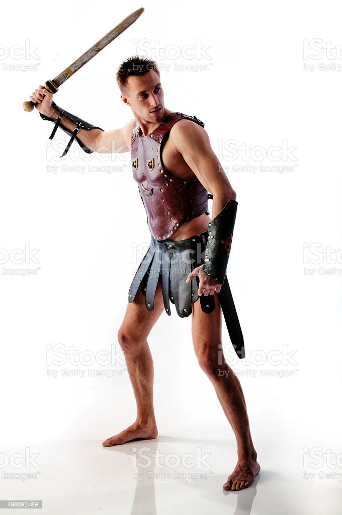 Ancient armed gladiator soldier with sword in battle pose isolated stock photo