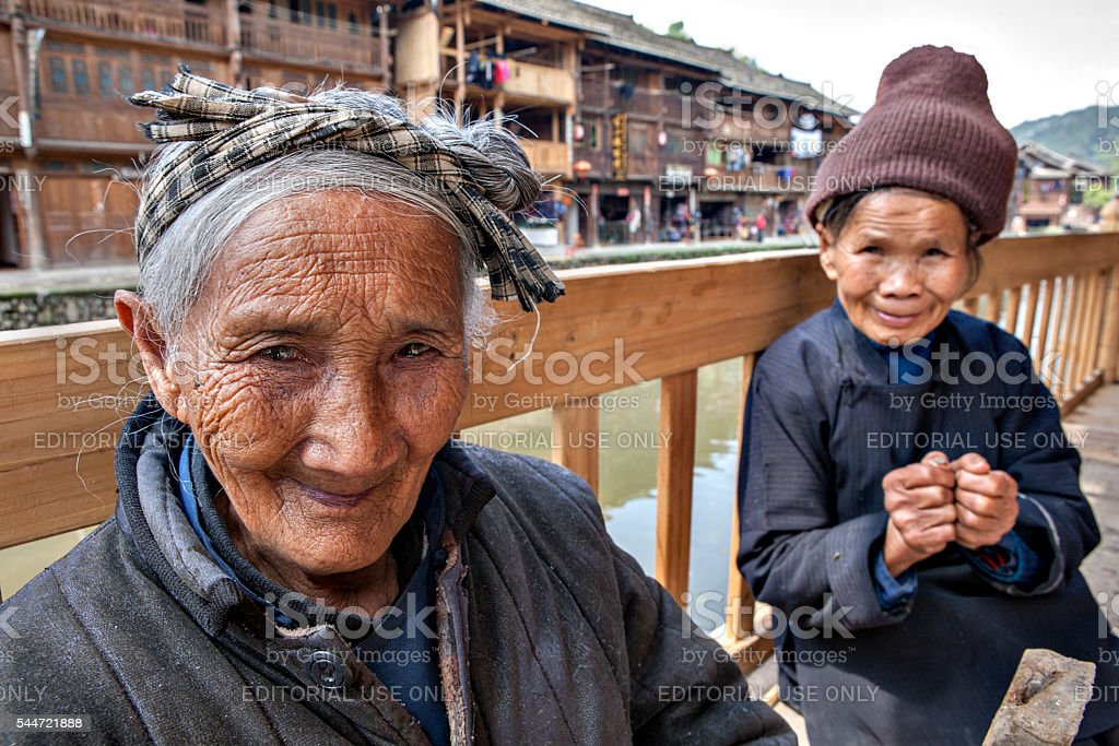 Ancient Asian Peasant woman resting on bench in Chinese countryside. stock photo