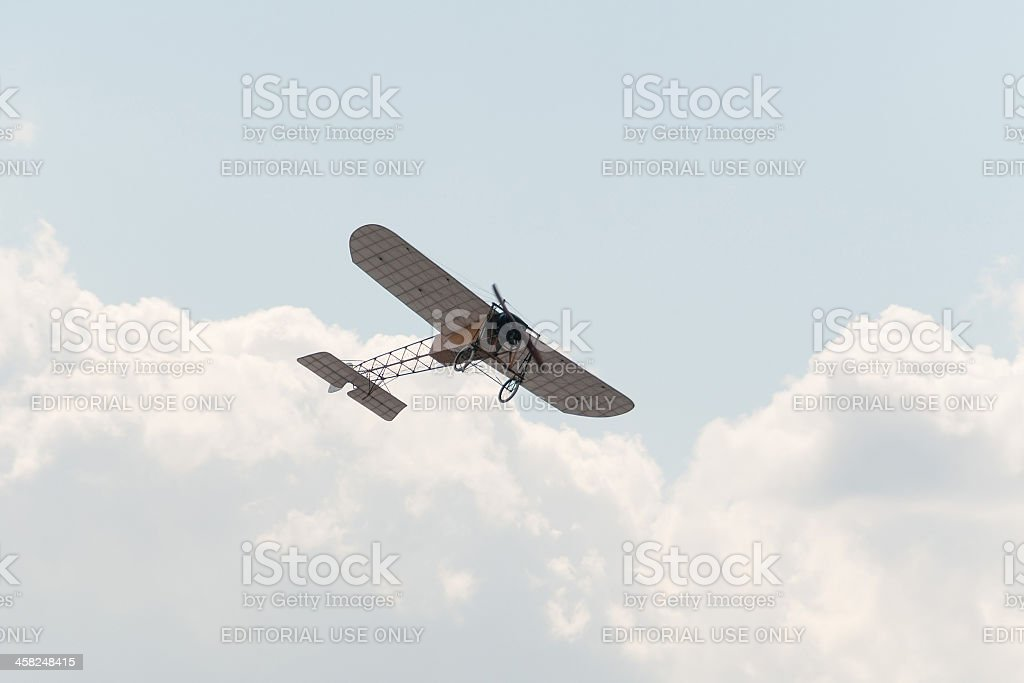 Ancient Blériot XI Gnome aircraft flies against blue sky background royalty-free stock photo