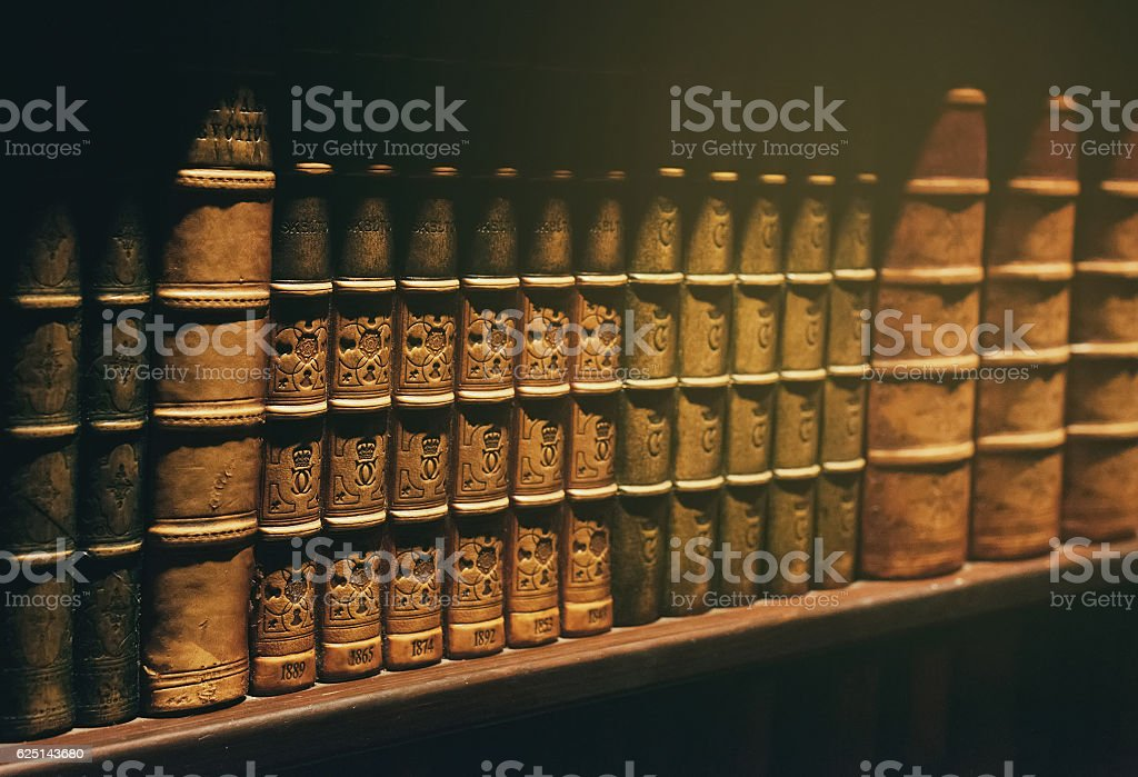Ancient books on wooden shelf. stock photo