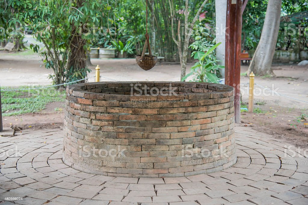 Ancient brick well and Bamboo Basket for dip up water stock photo