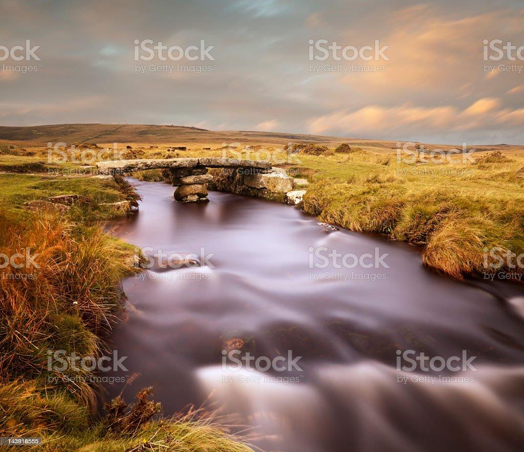 Ancient bridge across river on Dartmoor in evening light. stock photo