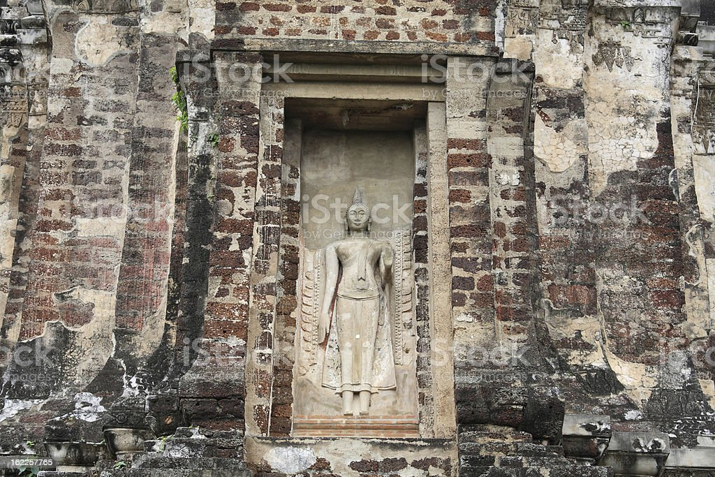Ancient Buddha statue attached on old brick pagoda stock photo