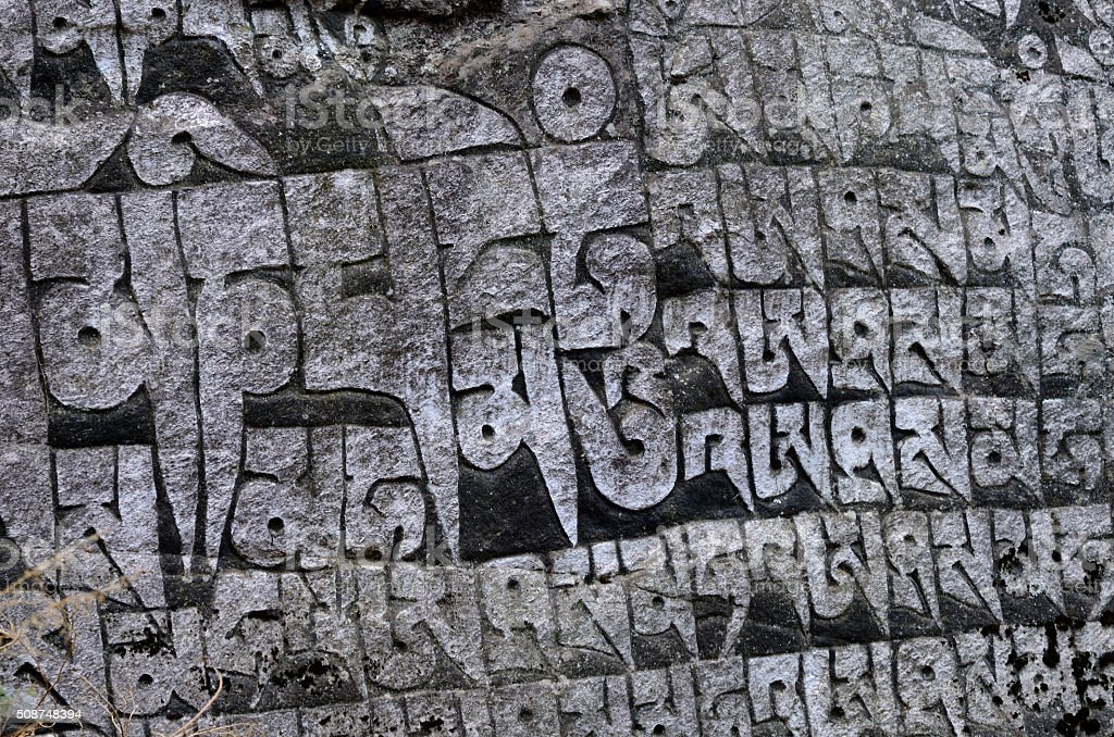 Ancient buddhist carved stone wall with sacred religious mantras,Nepal stock photo