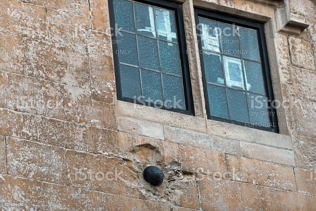 Ancient Cannon Ball in Wall stock photo
