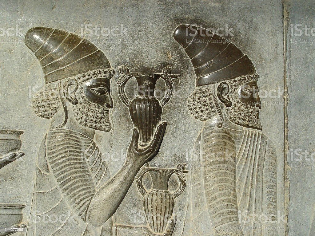 Ancient carving of a Persian man holding a jug stock photo
