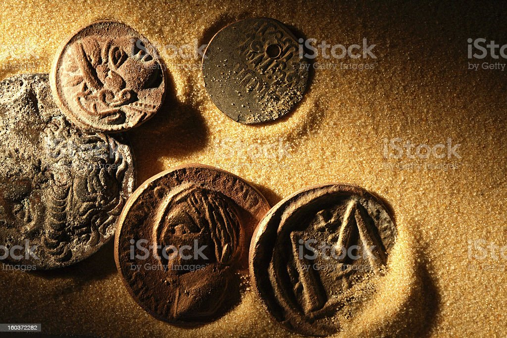 Ancient coins laying in golden sand stock photo
