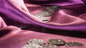 Ancient coins on purple satin
