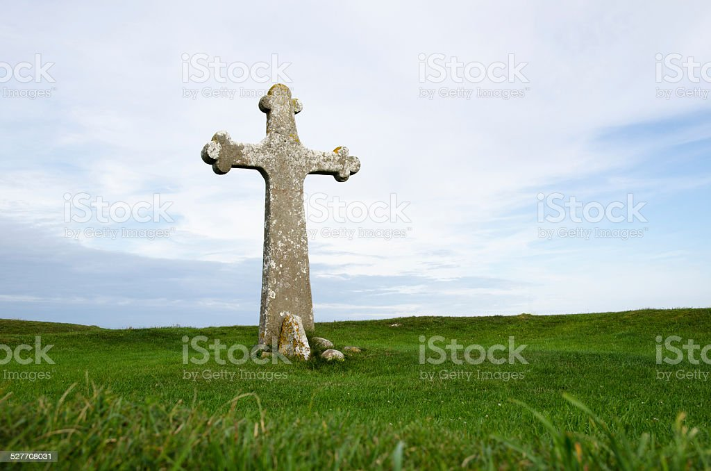 Ancient cross surrounded of green grass stock photo