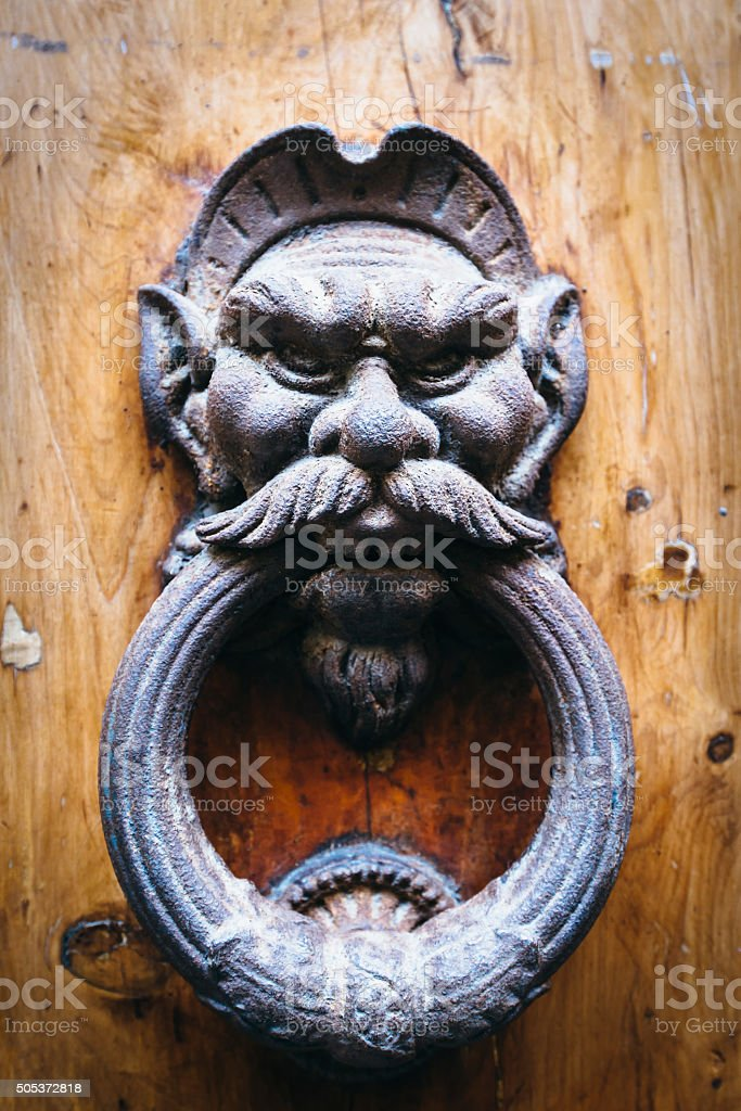 Ancient Door Knocker Decorated With Devil stock photo