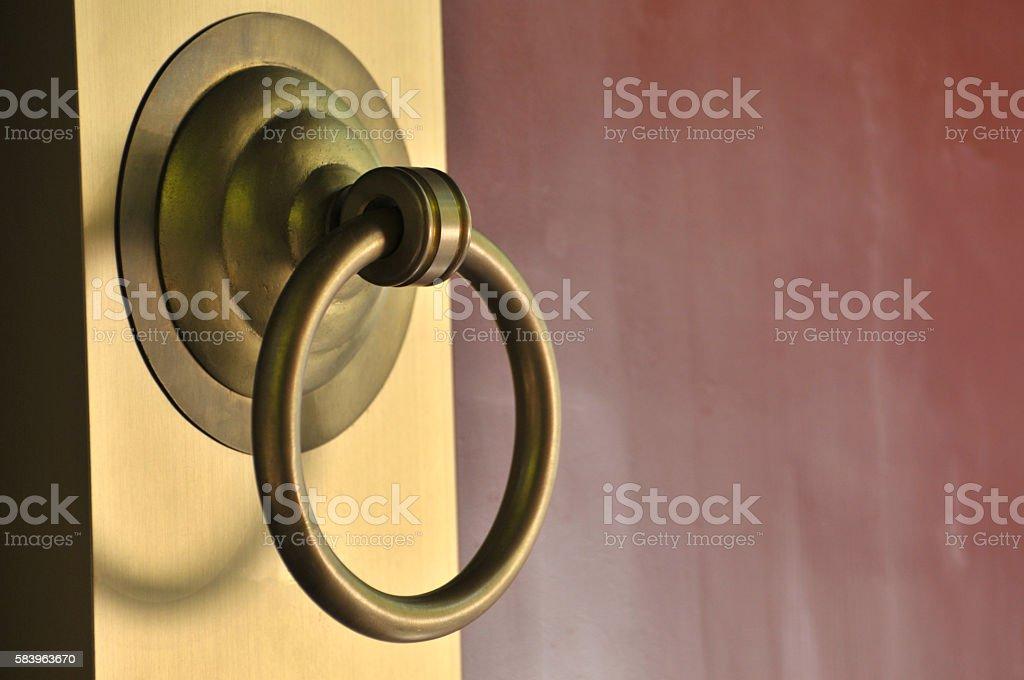 Ancient door knocker on a wood stock photo