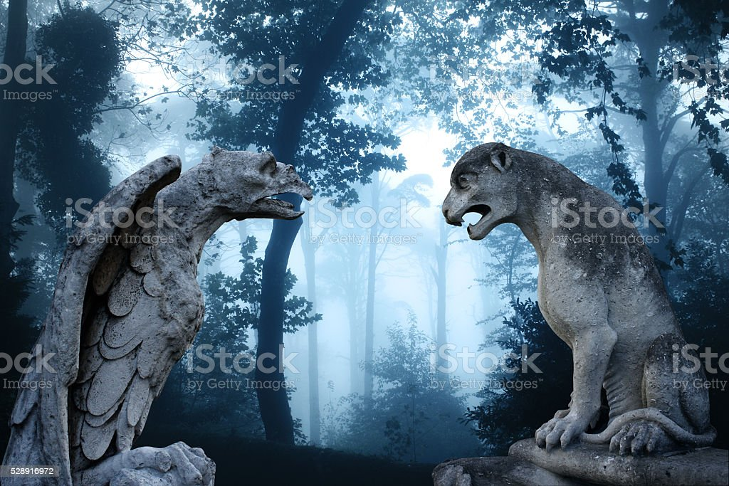 Ancient eagle and lion statues in misty forest stock photo