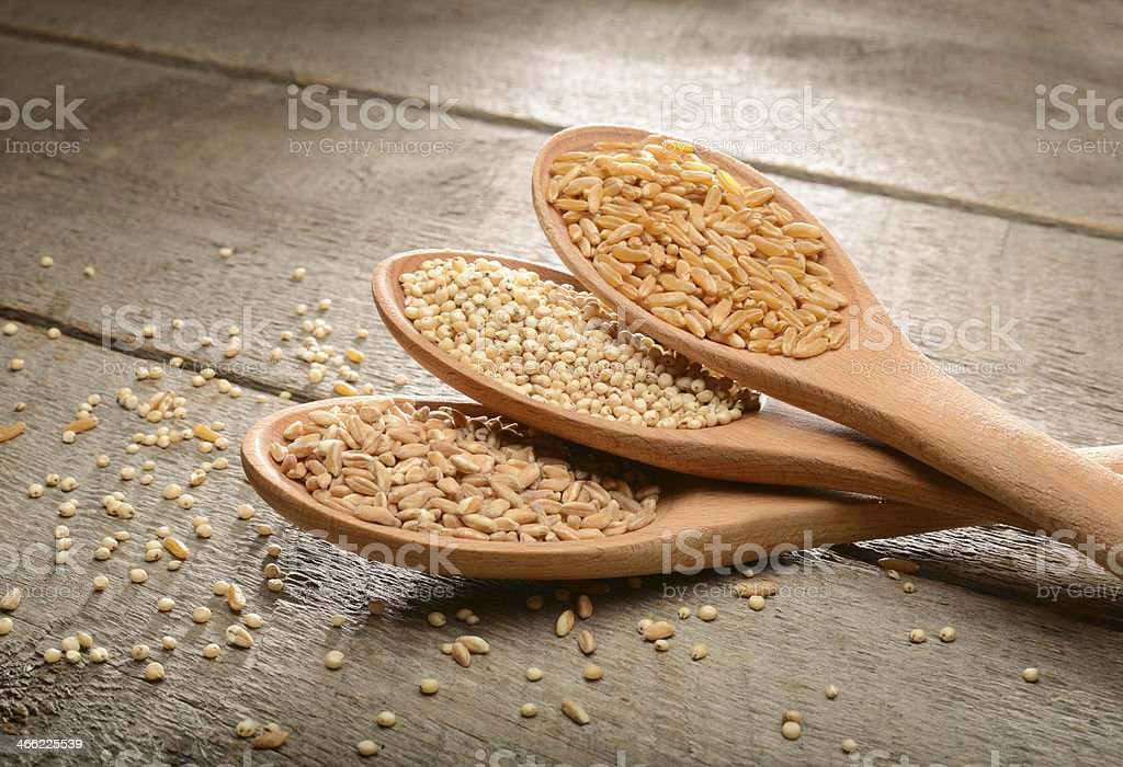 Ancient food grains on wood background stock photo