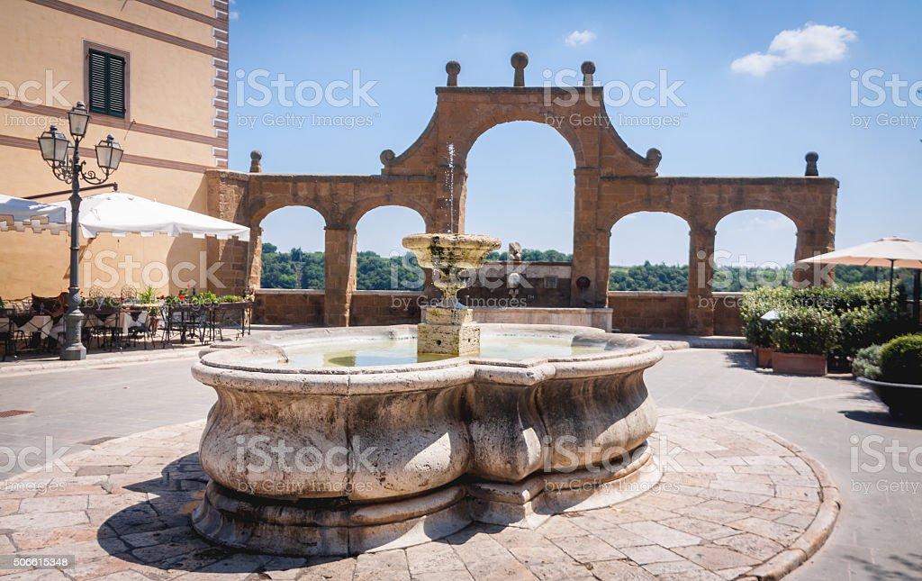 Ancient Fountain and arches in Repubblica square, in Pitigliano, stock photo