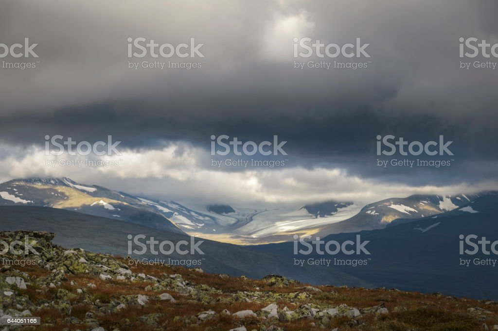 Ancient glaciers landscape in sunlight under stormy and dramatic sky stock photo