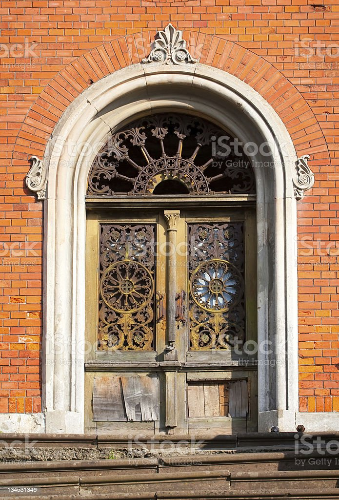 Ancient grungy doors in a brick wall royalty-free stock photo