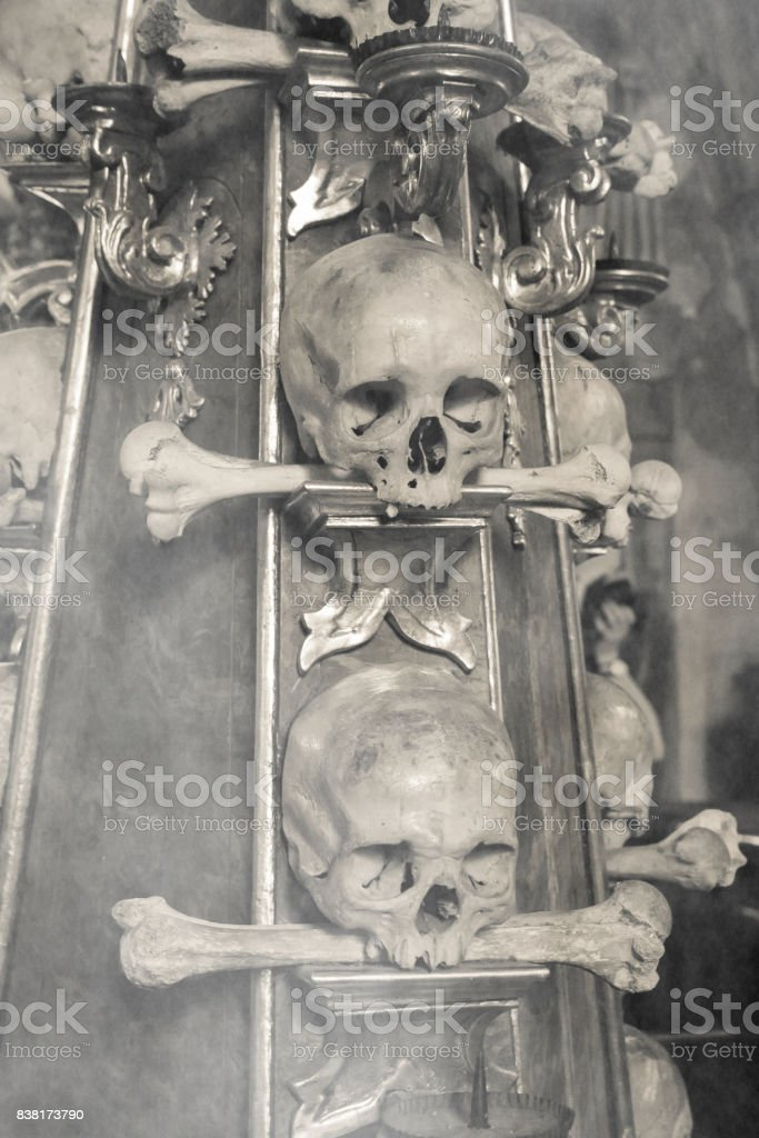 Ancient human skull and bone decoration in Sedlec with fog, Czech republic. stock photo