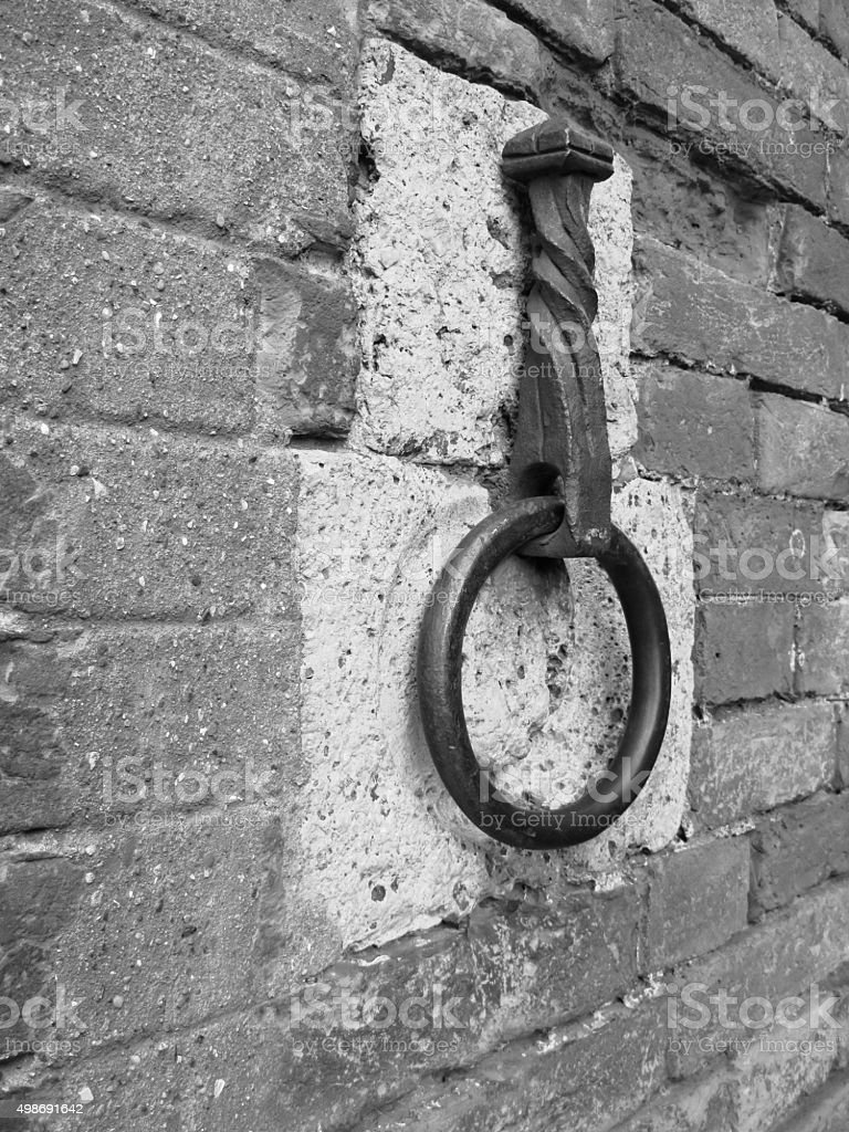 Ancient iron hoop hanging on stone wall stock photo