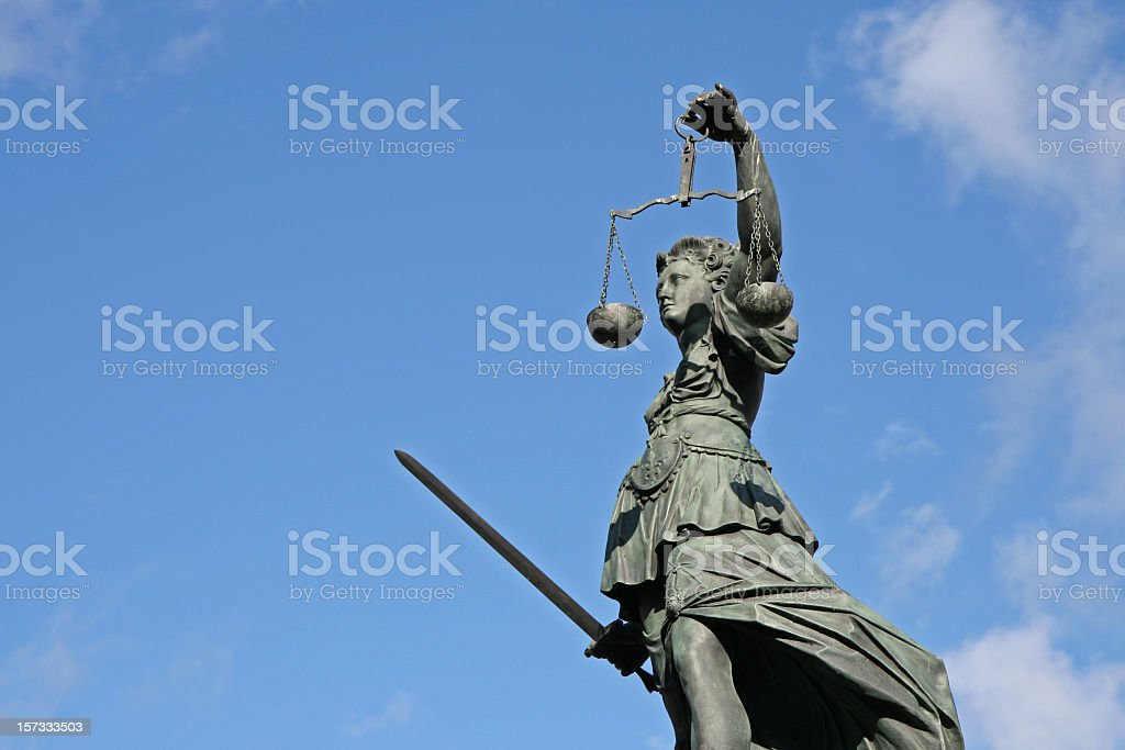 ancient Justicia statue with scale and sword from left stock photo