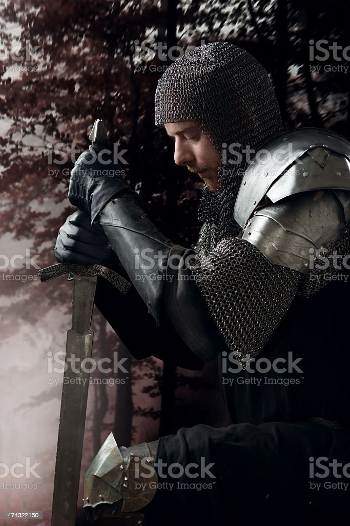 Ancient knight standing on one knee stock photo