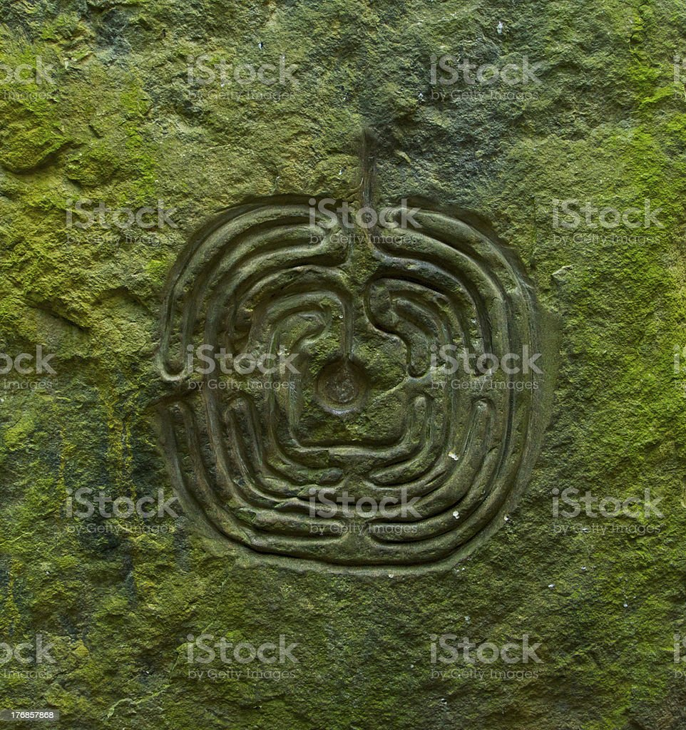 Ancient labyrinth cut in stony wall stock photo