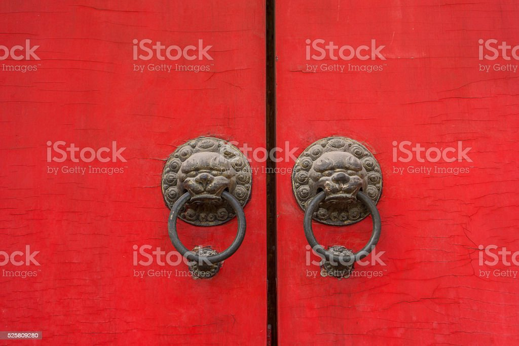 ancient lion knocker on red wooden door stock photo