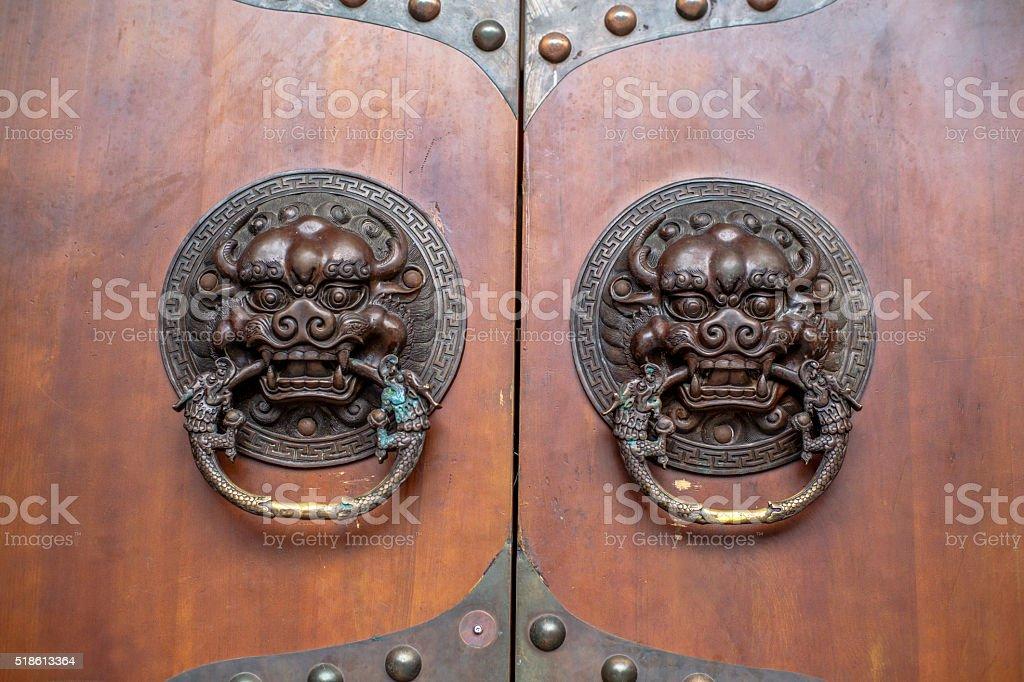 ancient lion knocker on wooden door stock photo