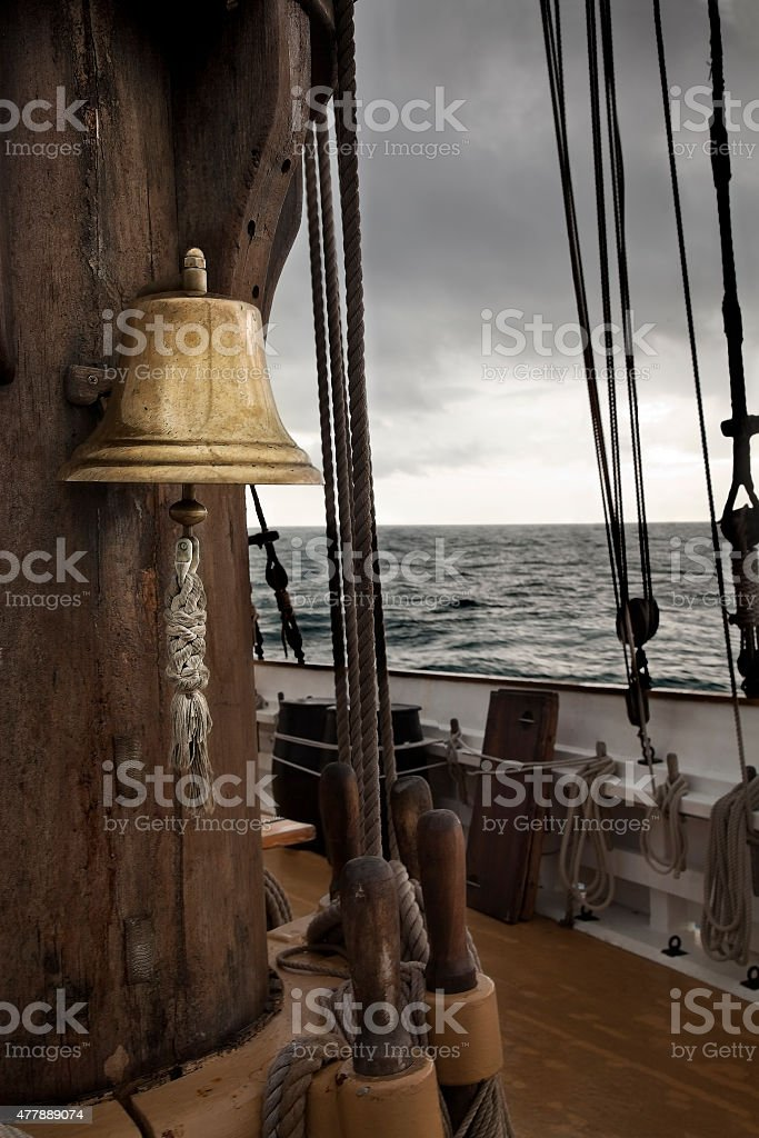 Ancient navigation bell and riggings on deck stock photo