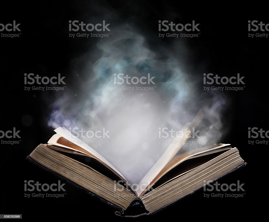 Ancient open book in the magical smoke stock photo