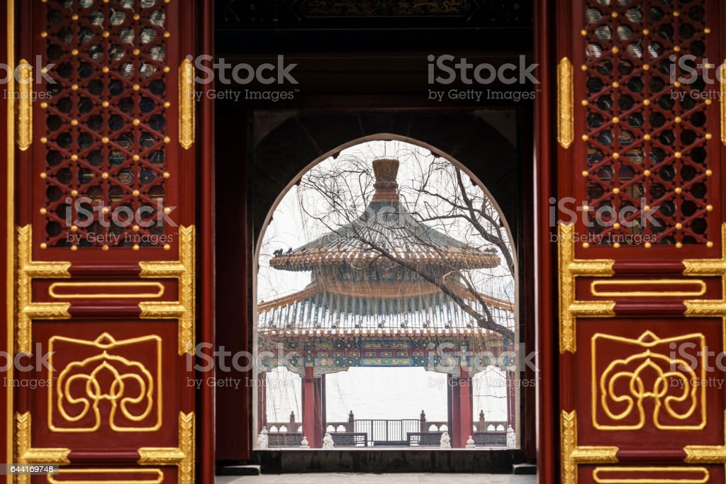 ancient pavilion seen from arch door of a temple in winter stock photo