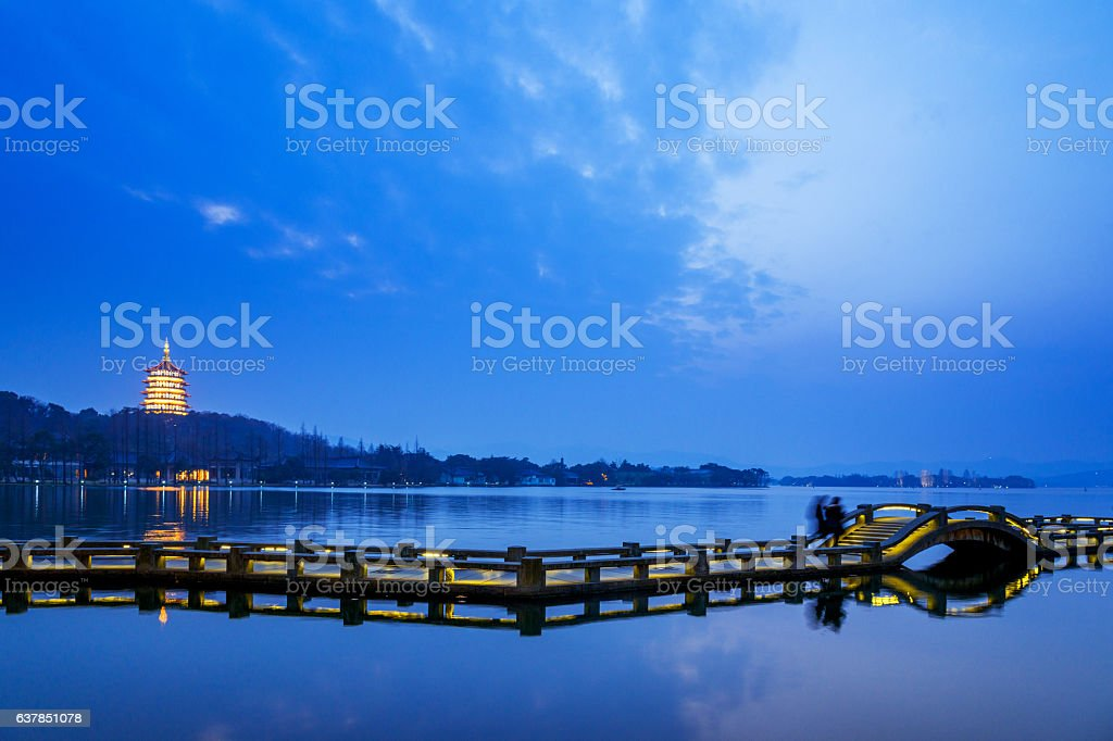 ancient pedestian bridge on water at twilight stock photo