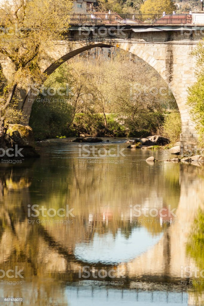 Ancient roman stone bridge reflected in river water in galicia spain stock photo