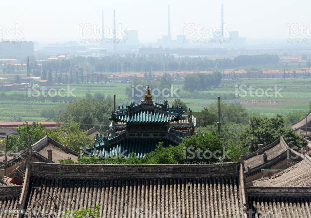 Ancient roof of Wusutu Zhao Buddhist Monastery on a background of modern Hohhot city, Inner Mongolia stock photo