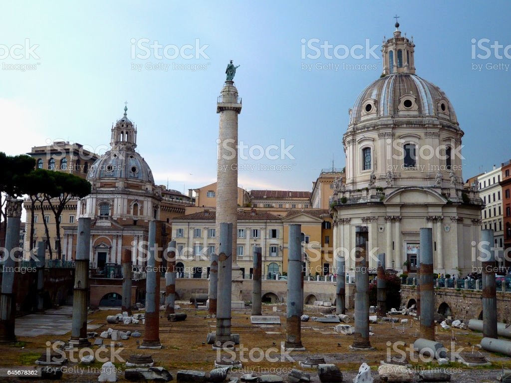 Ancient ruins of the Trajan's forum in Rome, Italy. Imperial forum traiani and Santa Maria di Loreto Church. Ancient roman ruins with Trajan's column under blue sky. stock photo