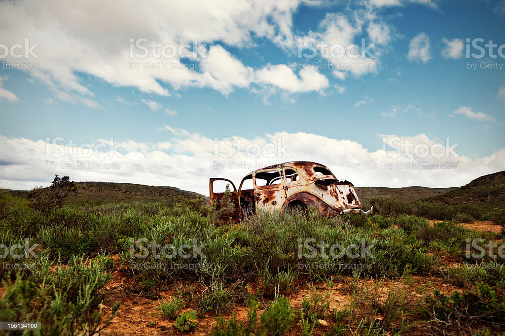 Ancient, rusted car body abandoned in remote countryside royalty-free stock photo
