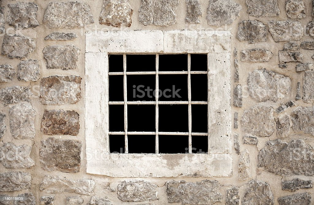 Ancient stone prison wall with metal window bars royalty-free stock photo
