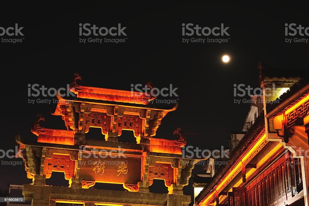 Ancient stone torii and eternal moon stock photo