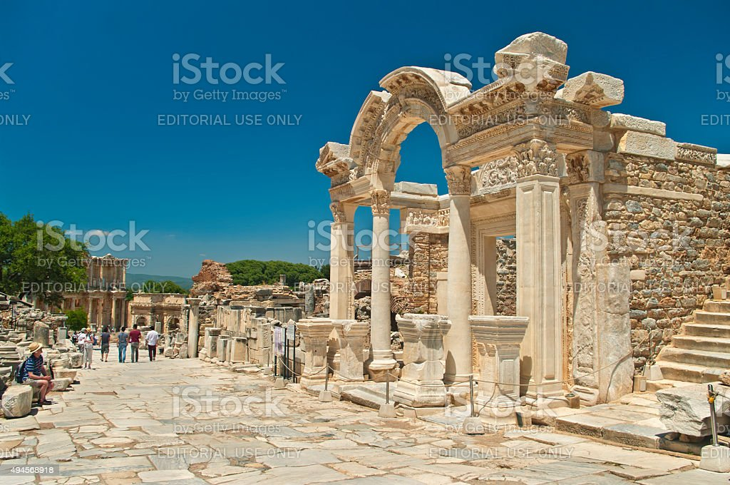 ancient temple ruins with tourists walking around stock photo