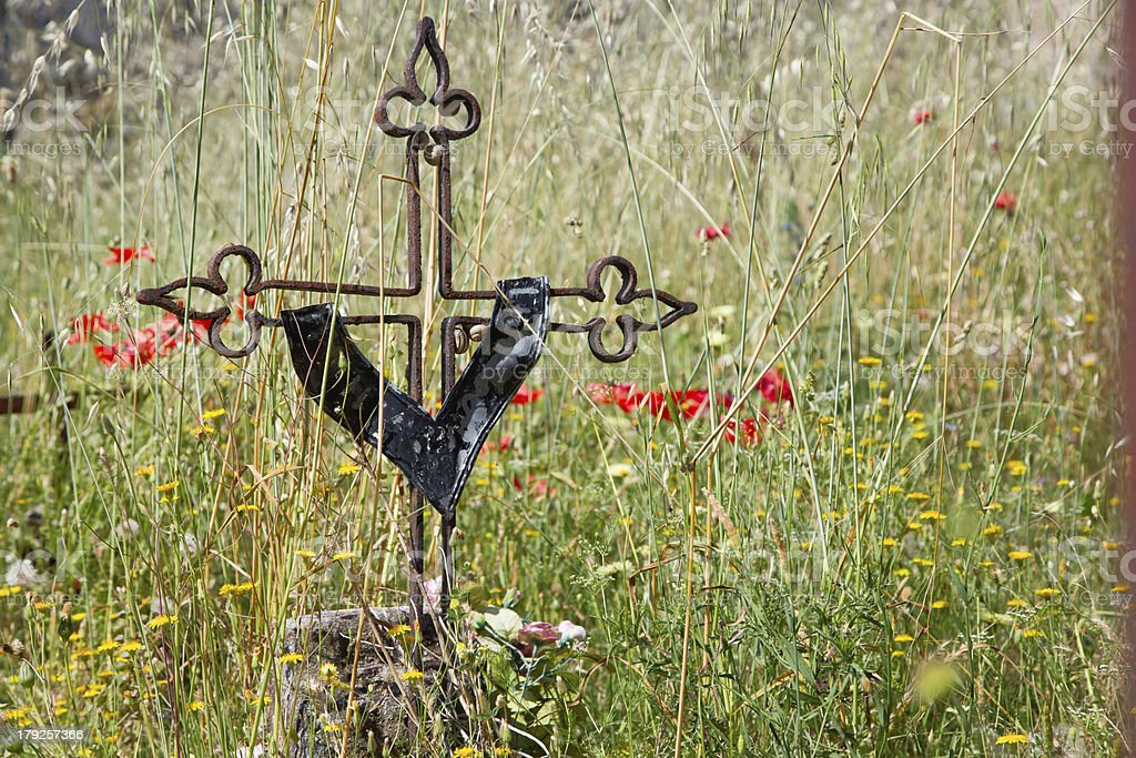 Ancient tomb with iron cross between flowers, Tuscany royalty-free stock photo