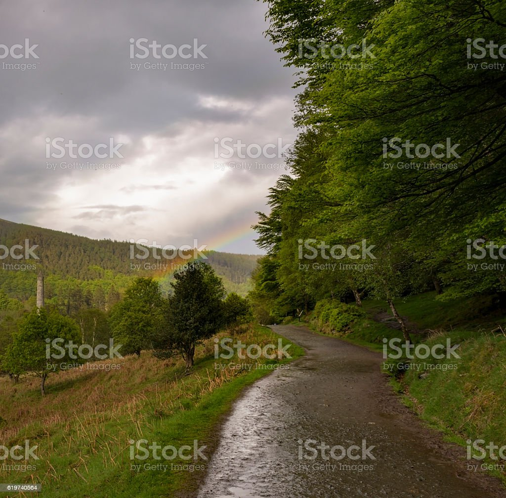 Ancient tower of Glendalough monastery with rainbow in bad weather stock photo