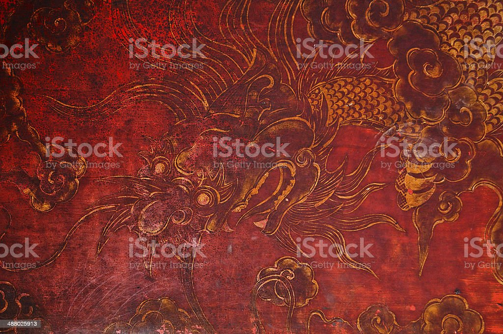 Ancient vintage golden painting of dragon on red wooden wall stock photo