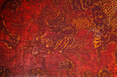 Ancient vintage golden painting of dragon on red wooden wall