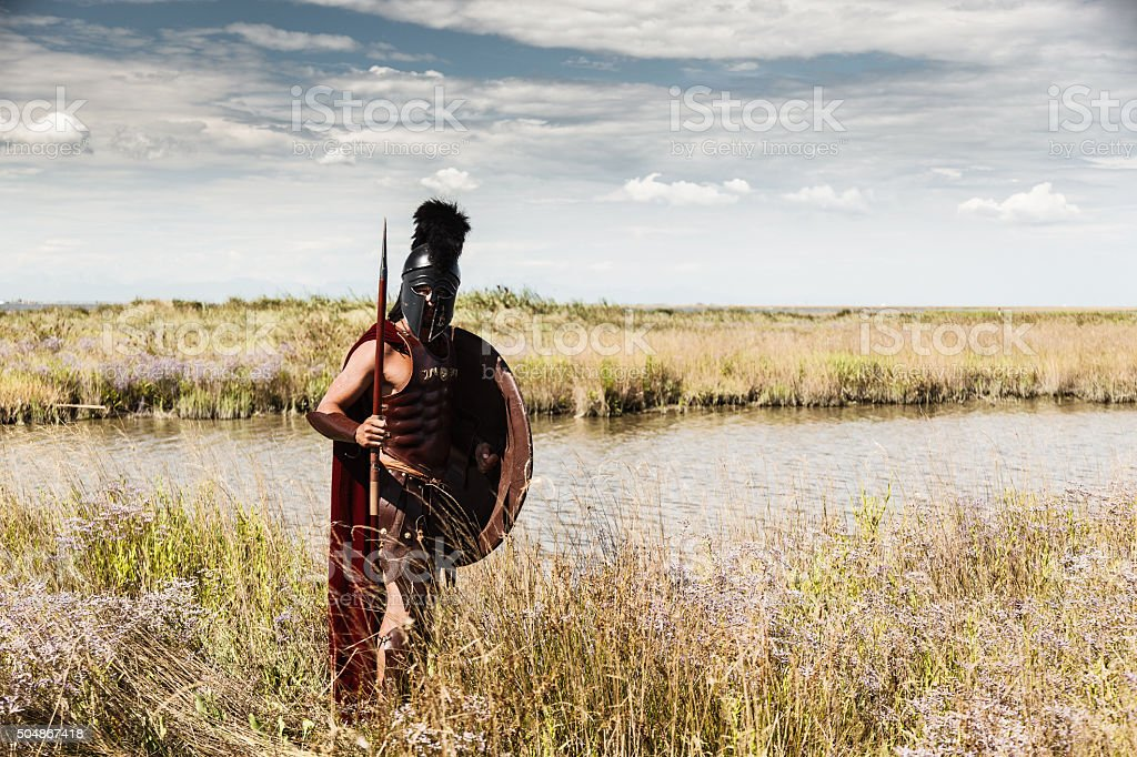 Ancient warrior in armor with Spear, Shield and Helmet stock photo