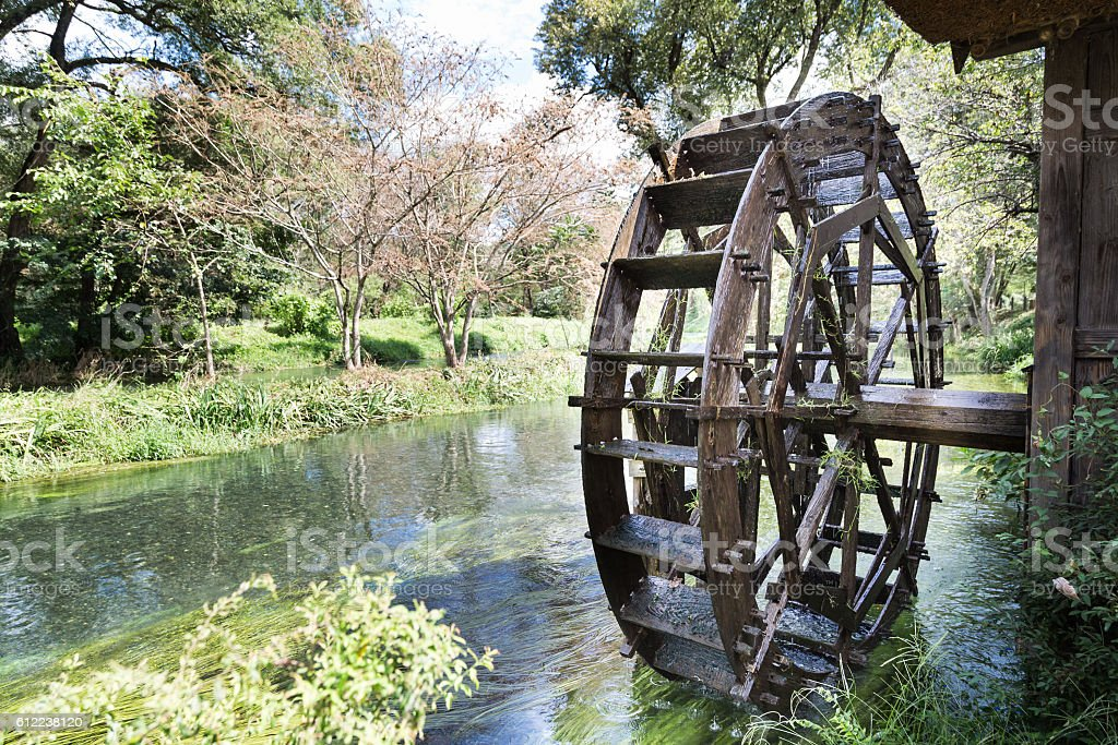 Ancient water wheel within serene and scenic river stock photo