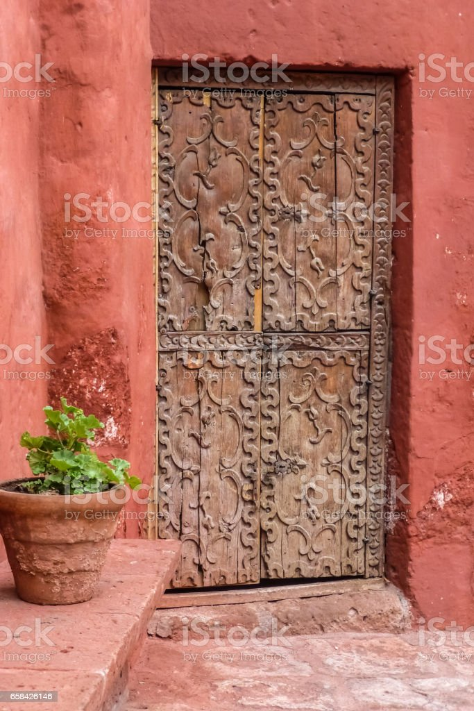 Ancient wooden door with ornamental carvings and flower tub, Santa Catalina Monastery, Arequipa stock photo