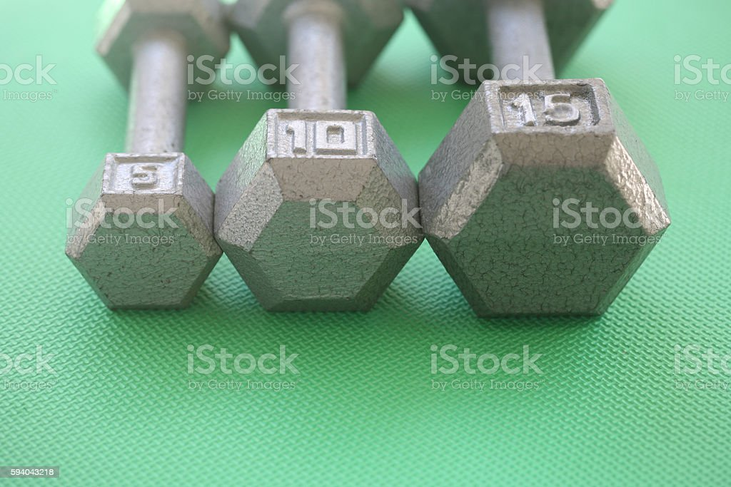 5, 10 and 15 pound weights in a row stock photo