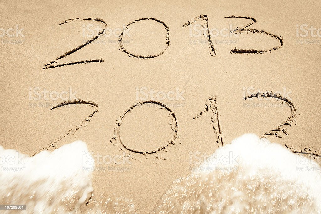 2012 and 2013 written in sand with waves royalty-free stock photo