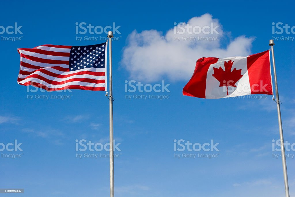 A US and Canadian flag against a blue sky stock photo
