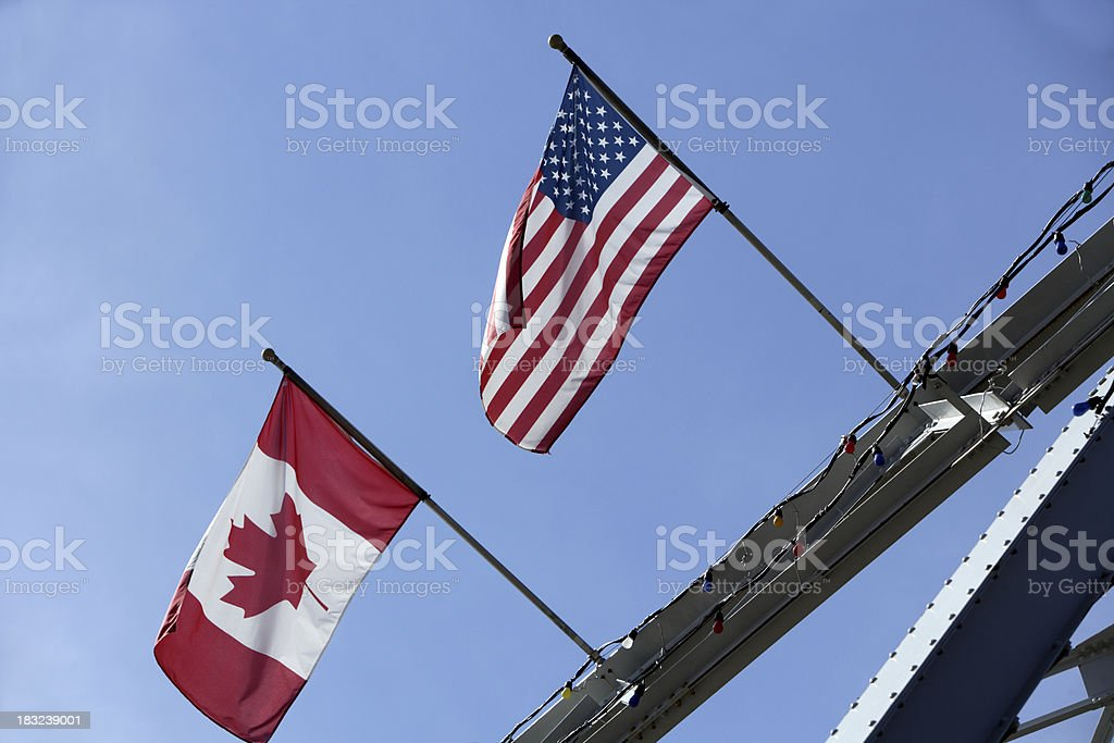 USA and Canadian flag blowing in the wind outside royalty-free stock photo